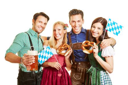 octoberfest: Grupo de amigos felices celebrando Oktoberfest con cerveza y pretzel en Baviera
