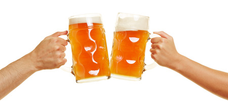 Two hands clinking beer glasses for a cheer