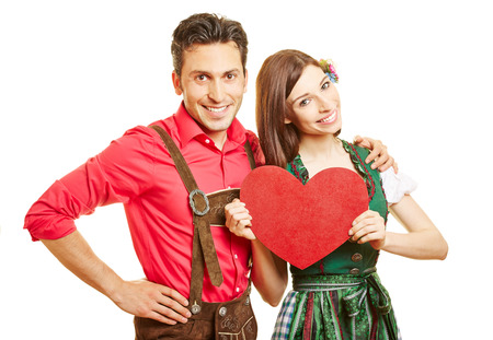 dirndl dress: Happy couple in dirndl dress and leather pants with a red heartin Bavaria
