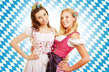 dirndl dress: Two smiling women in pink dirndl dress in Bavaria