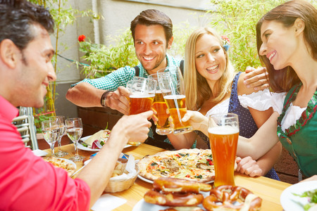 Happy friends in bavaria celebrating with beer and pizza in summer