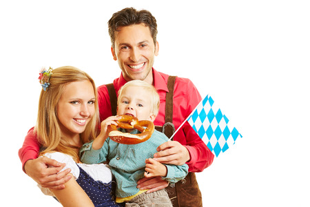 pretzel: Happy bavarian family smiling with pretzel and flag