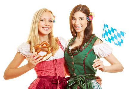 dirndl dress: Two happy bavarian women in dirndl dress with pretzel and flag Stock Photo