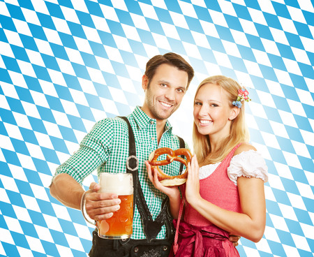 Happy couple celebrating Oktoberfest in Bavaria with beer and pretzel photo