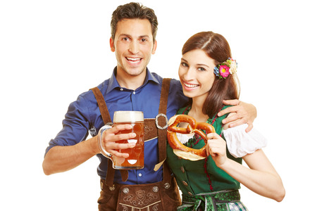 wiesn: Smiling man and happy woman at Oktoberfest with beer and pretzel in their hands