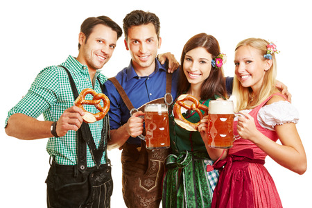 Happy group of people with beer and pretzel having fun at Oktoberfest