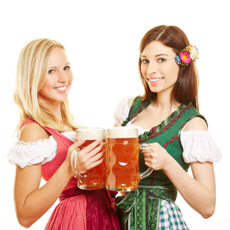 dirndl dress: Two happy women in dirndl dress with beer in Bavaria
