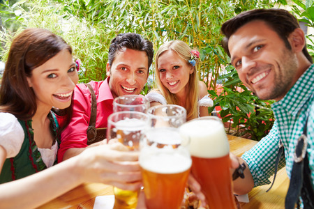 Smiling friends in beer garden clinking their glasses in summer photo