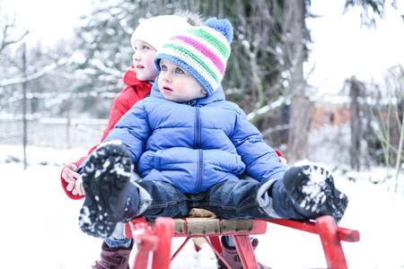 sledding: Two little children sledding together in winter in snow Stock Photo