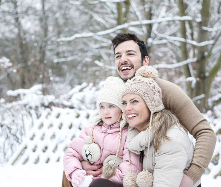 Portrait of a happy family in winter with daughter photo