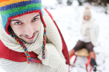 Man carrying woman in sled though snow in winter photo