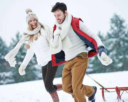 Happy couple with sled running through snow in winter
