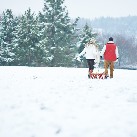 to go sledding: Couple pulling a sled together in snowy winter landscape