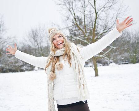 stretched out: Happy woman standing in winter snow with her arms stretched out