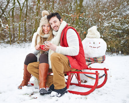 Happy couple in winter drinking tea and sitting on a sled photo