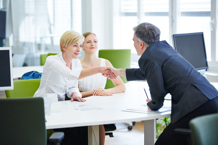Business people at table shaking hands in a meeting photo
