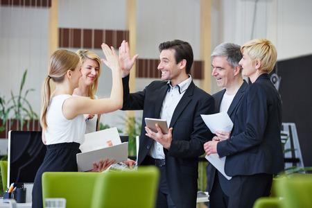 オフィスでハイファイブを与えるビジネス人々 の成功したチーム 写真素材