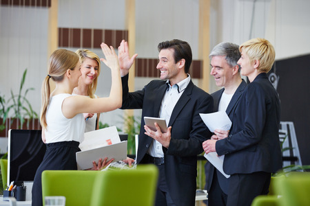 company employee: Successful team of business people giving high five in the office Stock Photo