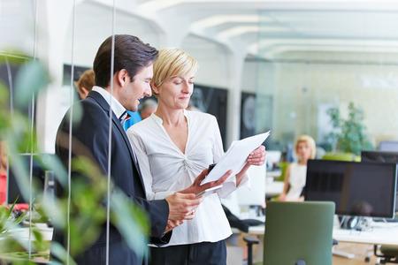 ejecutivo en oficina: Dos hombres de negocios hablando de un contrato en la oficina Foto de archivo