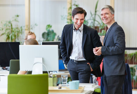 Two happy business people laughing during office break