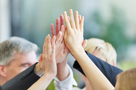 manos trabajo: Muchas manos que animan dan altos cinco en la oficina de negocios