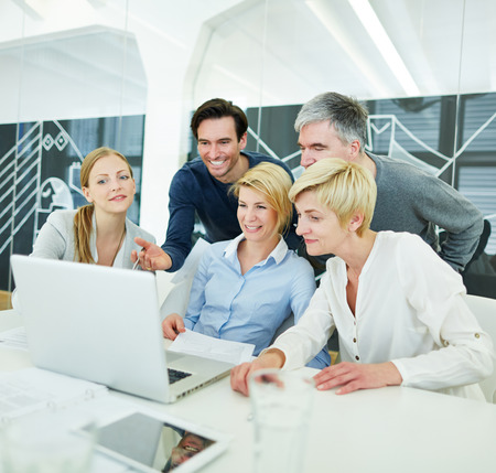 Happy business people getting computer training in the office