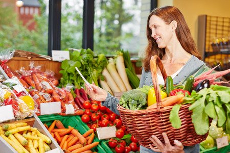 Smiling elderly woman with shopping list buying groceries and vegetables in a supermarket photo