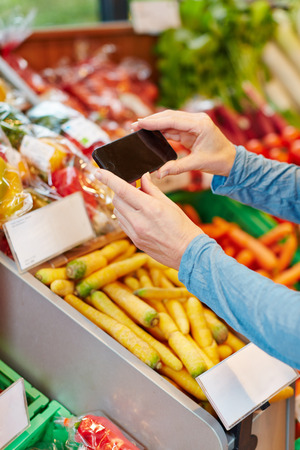 App in smartphone scanning barcode for price comparison in supermarket photo