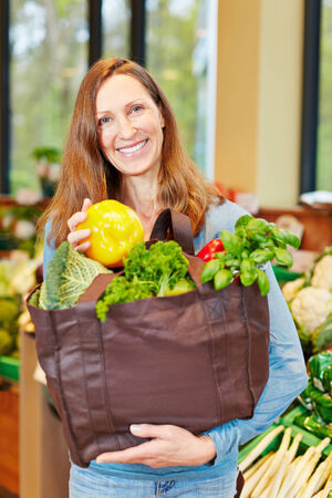 Smiling woman shopping for vegetables in a supermarket photo