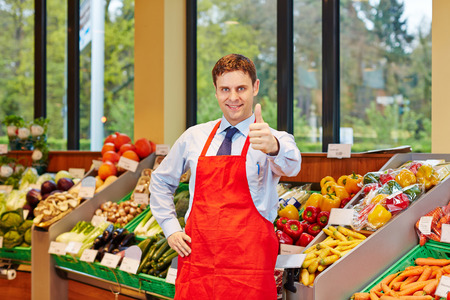 grocer: Smiling store manager in a supermarket holding his thumbs up