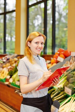 censo: Mujer joven sonriente como vendedor con el portapapeles en supermarkt Foto de archivo