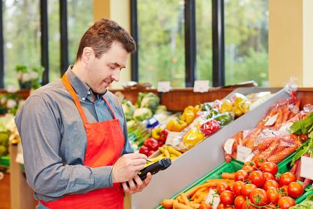Gerente de tienda en el supermercado usando un terminal de registro de datos móviles