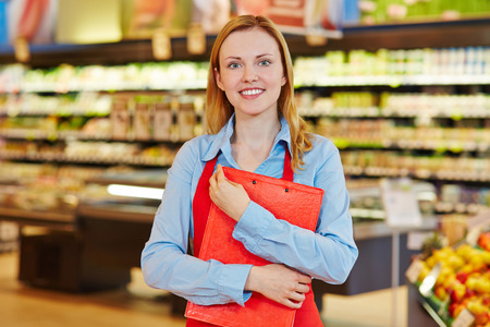Young female supermarket employee holding a clipboard photo