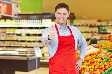 tiendas de comida: Gerente de la tienda feliz celebración de sus pulgares para arriba en un supermercado