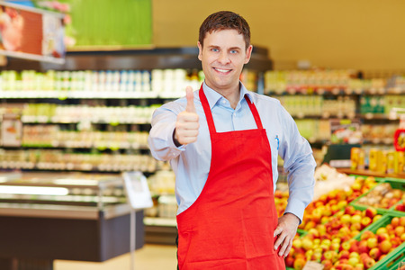 Happy store manager holding his thumbs up in a supermarket