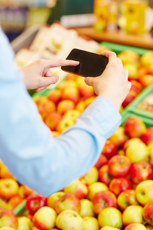 Hand scanning information of fresh fruit with a smartphone in a supermarket photo