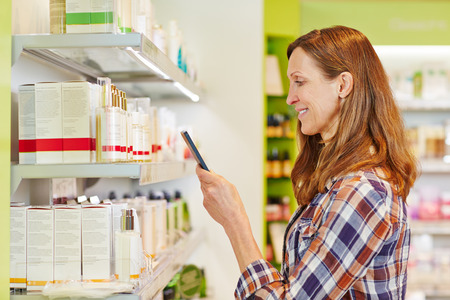 Personal Care: Woman scanning barcode of cosmetics in supermarket with her smartphone