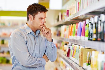 Hombre pensativo en el supermercado de tomar una decisión de compras sostenible