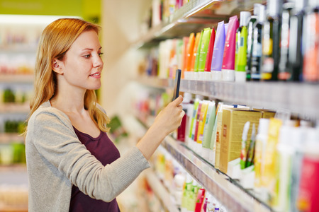 skin care products: Young woman comparing prices with a smartphone app in a drugstore