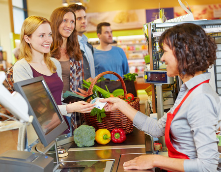 saleswomen: Smiling woman paying cash with Euro money bill at supermarket checkout Stock Photo