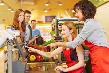 cassa supermercato: Commessa anziano che aiuta giovane donna al supermercato checkout Archivio Fotografico