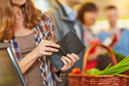 Hand of a woman looking for money in wallet at supermarket checkout
