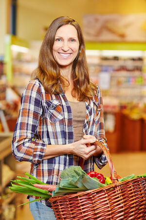 Smiling elderly woman carrying basket full of fresh vegetables in a supermarket photo
