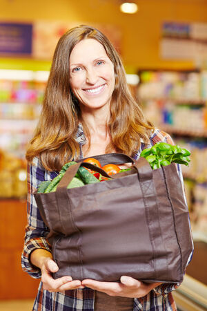 Attractive smiling woman in supermarket holding shopping bag full of vegetables photo
