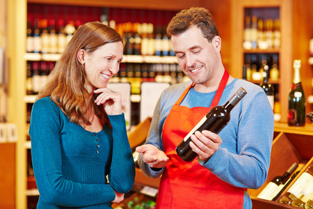 vendedor: Sommelier en tienda de vinos que mujer recomendación para botella de vino Foto de archivo