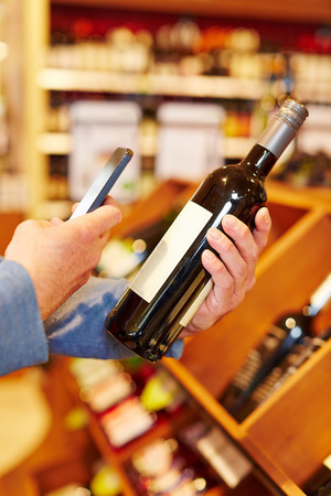 Price comparison with app in smartphone on bottle of red wine photo