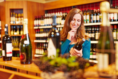 Smiling attractive woman with red wine bottle in organic food store photo