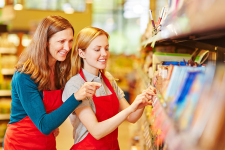 Young retal saleswoman trainee in supermarket getting help from staff photo