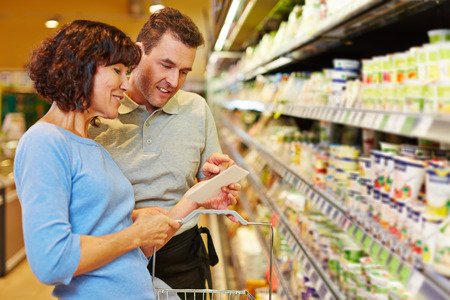 Smiling salesman helping elderly woman with her shopping list in a supermarket photo