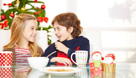 christmas tea: Two happy children eating cookies at christmas at the table Stock Photo